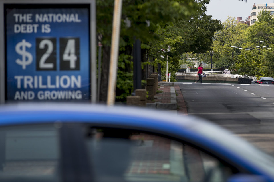 Photo -  In this April 29 photo, a sign displaying the size of the national debt is displayed along an empty K Street in Washington. [Andrew Harnik/associated press file photo]