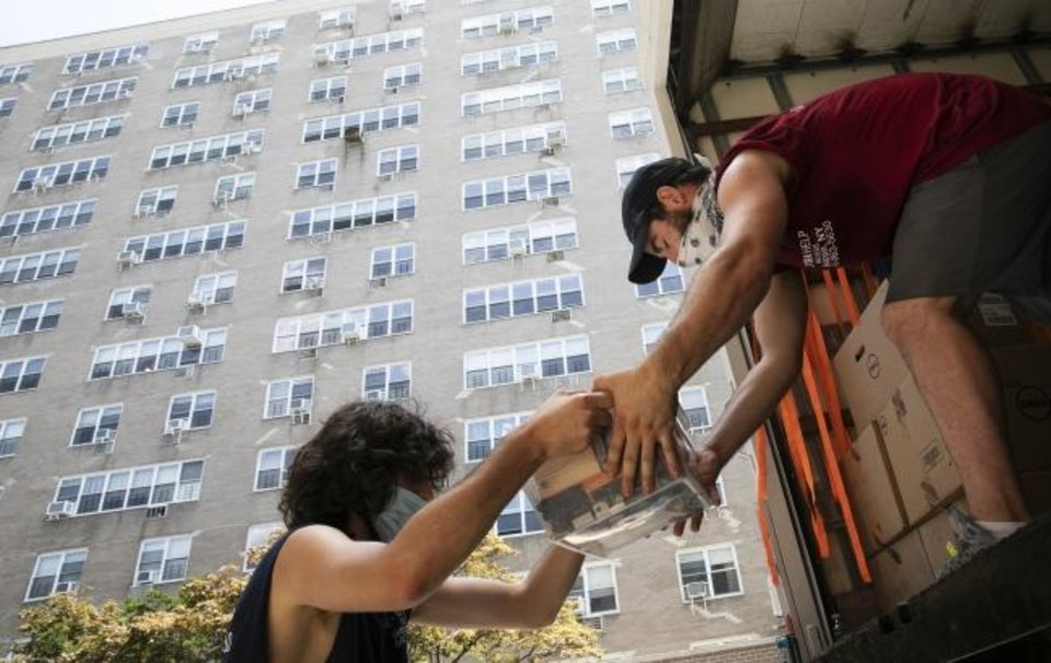 Photo -  Jakob Howell, left, and Matt Brown load boxes belonging to Joyce and Anil Lilly into a moving truck In The Bronx borough of New York. The Lillys are leaving their 14th-floor apartment and are moving to a town an hour's drive north, amid the coronavirus pandemic. [AP PHOTO]