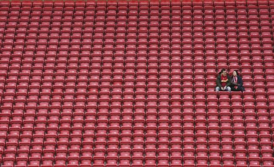 Photo -  People sit surrounded by empty seats as they wait for the start of the English Premier League soccer match between Liverpool and Bournemouth at Anfield stadium in England on March 7. [AP Photo/Jon Super]