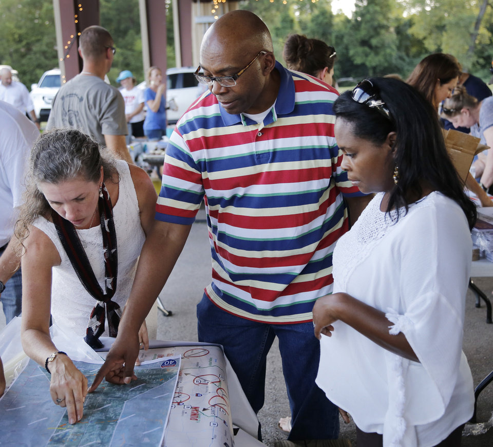 Photo - Joelle Volpe, left, shows Dr. James Taylor and his wife Raphala, the areas affected on the map of the proposed route after the Victimsofiminentdomain.com rally at Choctaw Creek Park, in Choctaw, against the eastern Oklahoma county turnpike leg that the Oklahoma Turnpike Authority has proposed building Friday, August 12, 2016. Photo by Doug Hoke, The Oklahoman