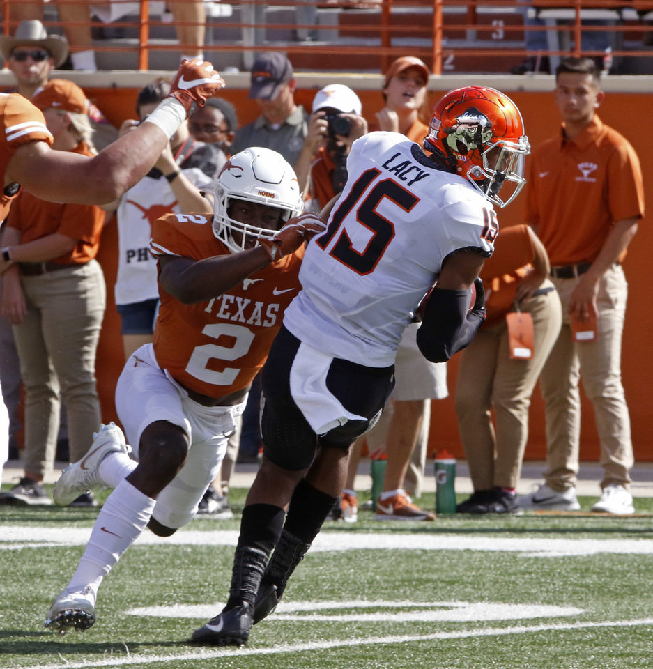 Photo - Oklahoma State receiver Chris Lacy (15) catches a pass against Texas defensive back Kris Boyd (2) during the first half of an NCAA college football game, Saturday, Oct. 21, 2017, in Austin, Texas. (AP Photo/Michael Thomas)