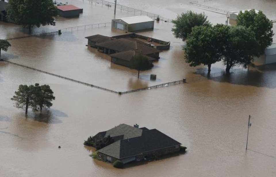 Photo - Homes are flooded on the Arkansas River in Tulsa, Okla., on Friday, May 24, 2019. The threat of potentially devastating flooding continued Friday along the Arkansas River from Tulsa into western Arkansas. (Tom Gilbert/Tulsa World via AP)