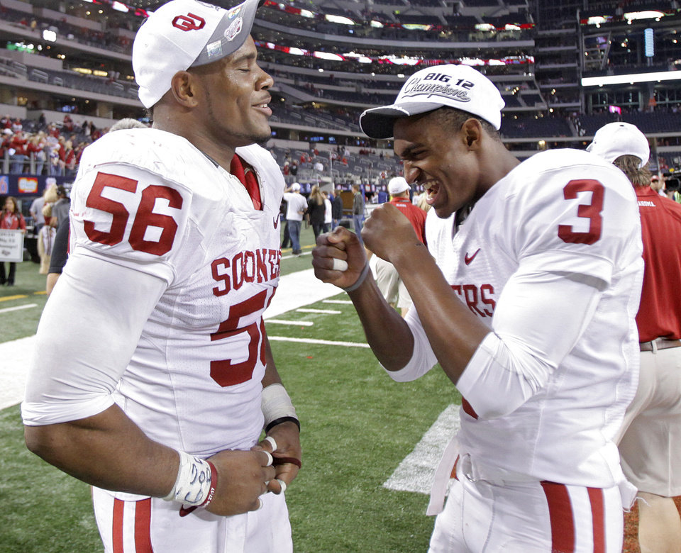 Photo - Oklahoma's Ronnell Lewis (56) and Joseph Powell (3) celebrate after the 23-20 win over Nebraska during the Big 12 football championship game between the University of Oklahoma Sooners (OU) and the University of Nebraska Cornhuskers (NU) at Cowboys Stadium on Saturday, Dec. 4, 2010, in Arlington, Texas.  Photo by Chris Landsberger, The Oklahoman