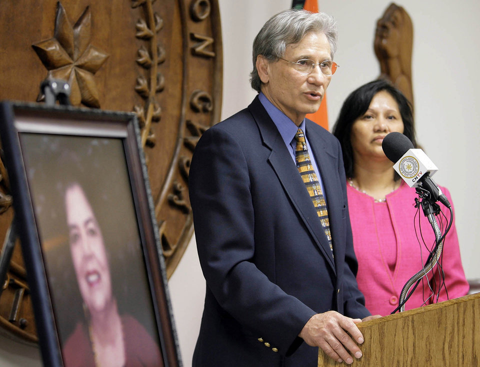 Photo - Chad Smith, principal chief of the Cherokees, stands with his wife, Bobby Gail, as he gives remarks next to a portrait of his friend and former chief Wilma Mankiller during a news conference at the Cherokee Nation headquarters in Tahlequah.  Photo by MICHAEL WYKE, Tulsa World