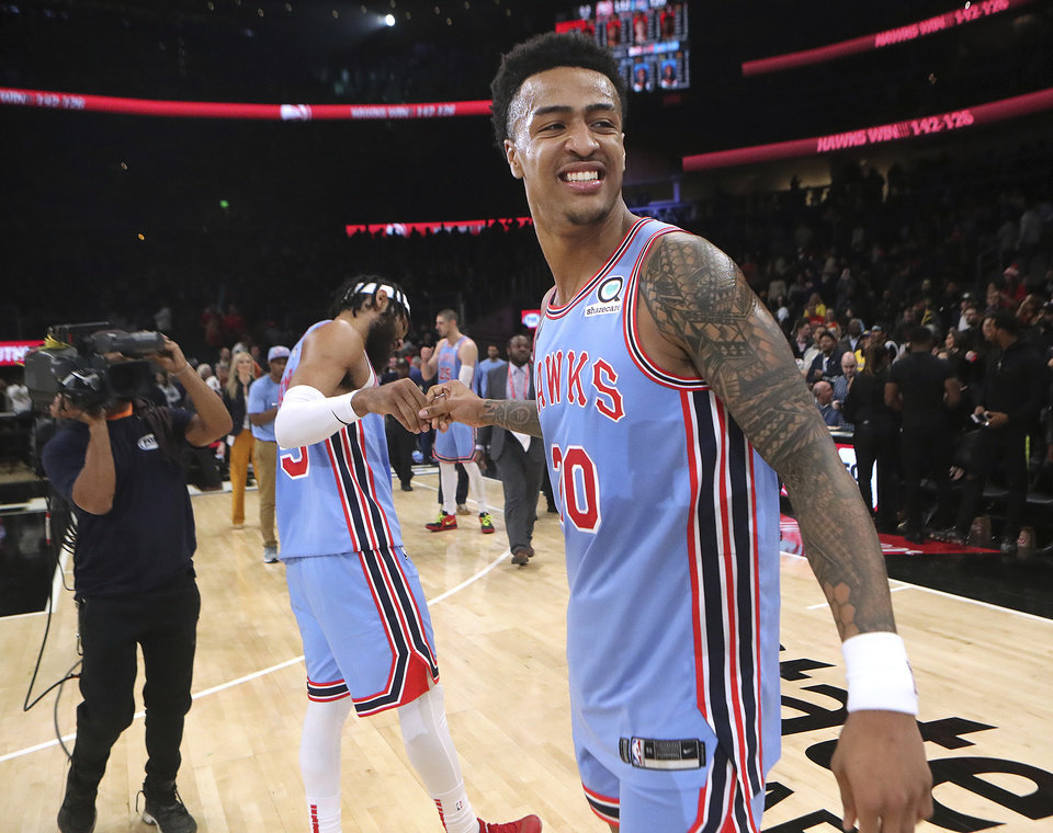 Photo - Atlanta Hawks forwards John Collins, right, and DeAndre Bembry celebrate a 142-126 victory over the Oklahoma City Thunder in an NBA basketball game on Tuesday, Jan. 15, 2019, at State Farm Arena in Atlanta. (Curtis Compton/Atlanta Journal-Constitution via AP)