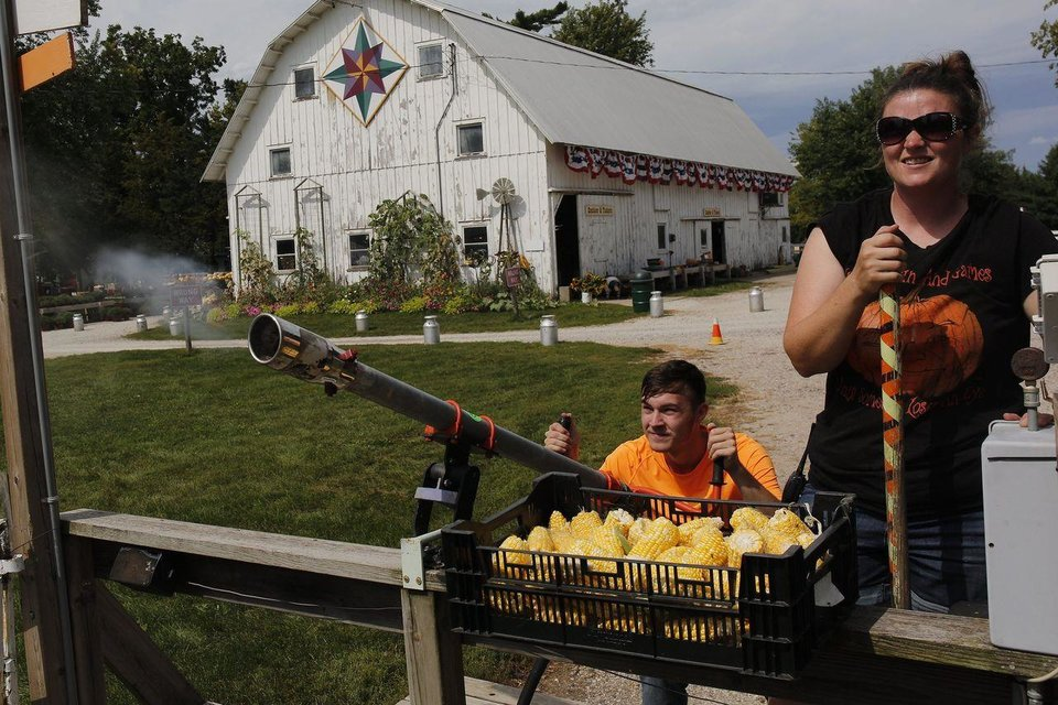 Photo - Ethan Kenoyer, 17, fires the corn cannon with Erin Howell-Conner looking on at Howell's, which charges $2 to fire four shots. PHOTO: RACHEL MUMMEY FOR THE WALL STREET JOURNAL