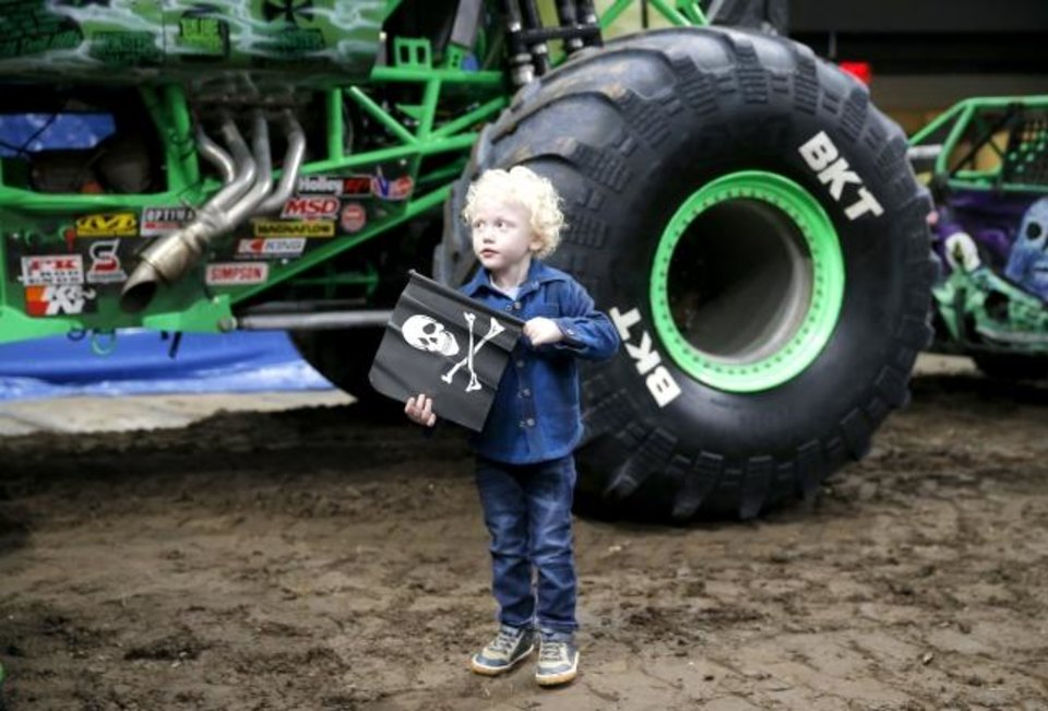 Photo -  Ryker Ammons, 4, of Yukon, Okla., stands in front the tire of Grave Digger at Chesapeake Energy Arena in Oklahoma City, Friday, Feb. 14, 2020.  [Sarah Phipps/The Oklahoman]