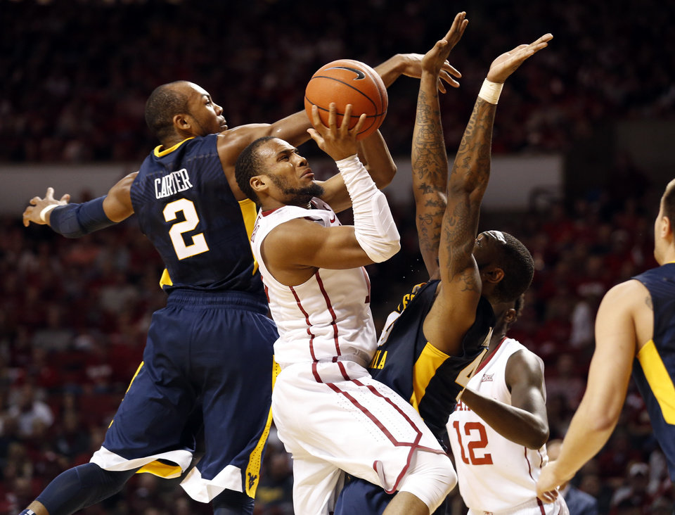 Photo - Oklahoma's Jordan Woodard (10) shoots as he drives between West Virginia's Jevon Carter (2) andElijah Macon (45) as the University of Oklahoma Sooner (OU) men defeat the West Virginia Mountaineers (WV) 70-68 in NCAA, college basketball at The Lloyd Noble Center on Jan. 16, 2016 in Norman, Okla. Photo by Steve Sisney, The Oklahoman