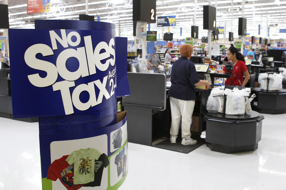 Photo - Shoppers make purchases at the Walmart store at 100 E. I-240 Service Road in south Oklahoma City, OK, Tuesday, July 30, 2013. This upcoming weekend will be sales tax free for purchases involving back-to-school supplies. Photo by Paul Hellstern, The Oklahoman