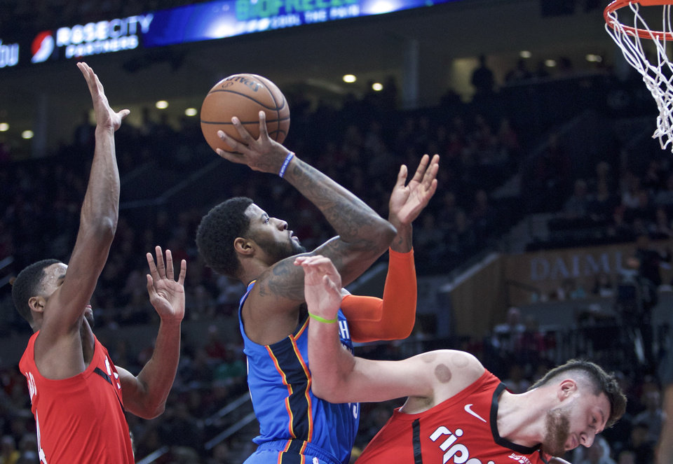 Photo - Oklahoma City Thunder forward Paul George, center, shoots between Portland Trail Blazers center Jusuf Nurkic, right, and forward Maurice Harkless during the first half of an NBA basketball game in Portland, Ore., Friday, Jan. 4, 2019. (AP Photo/Craig Mitchelldyer)