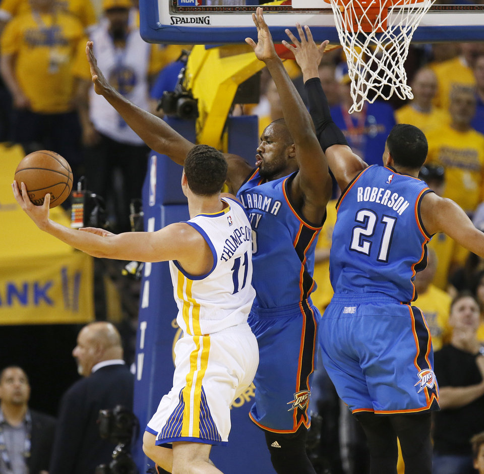 Photo - Oklahoma City's Serge Ibaka (9) and Andre Roberson (21) defend Golden State's Klay Thompson (11) during Game 5 of the Western Conference finals in the NBA playoffs between the Oklahoma City Thunder and the Golden State Warriors at Oracle Arena in Oakland, Calif., Thursday, May 26, 2016. Photo by Nate Billings, The Oklahoman