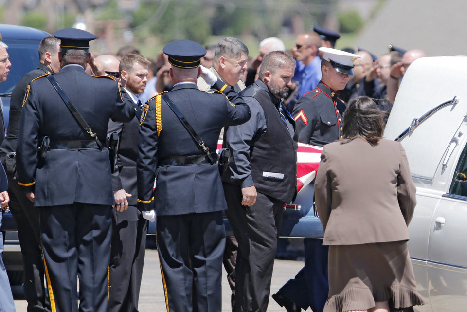 Photo -  An honor guard salutes the flag-draped casket of Logan County Deputy David Wade on Monday during his funeral service. Wade died last week after being shot while helping to serve an eviction notice. [Photos By Steve Gooch, The Oklahoman]