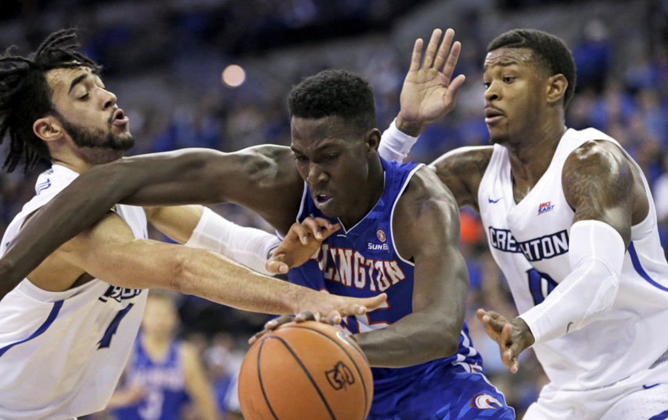 Photo - Texas-Arlington's Kevin Hervey (25) is defended by Creighton's Marcus Foster (0) and Creighton's Ronnie Harrell Jr., left, during the second half of an NCAA college basketball game in Omaha, Neb., Monday, Dec. 18, 2017. Creighton won 90-81. (AP Photo/Nati Harnik)