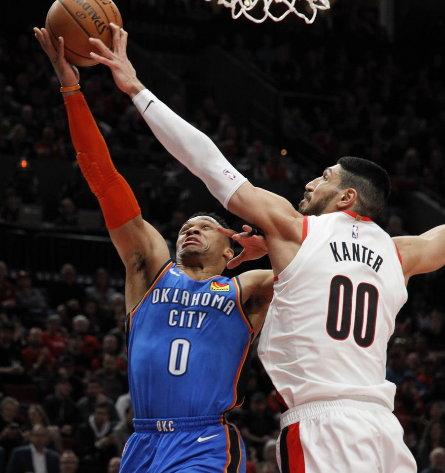 Photo - Oklahoma City Thunder guard Russell Westbrook, left, has his shot blocked by Portland Trail Blazers center Enes Kanter, right, during the first half of Game 1 of a first-round NBA basketball playoff series in Portland, Ore., Sunday, April 14, 2019. (AP Photo/Steve Dipaola)