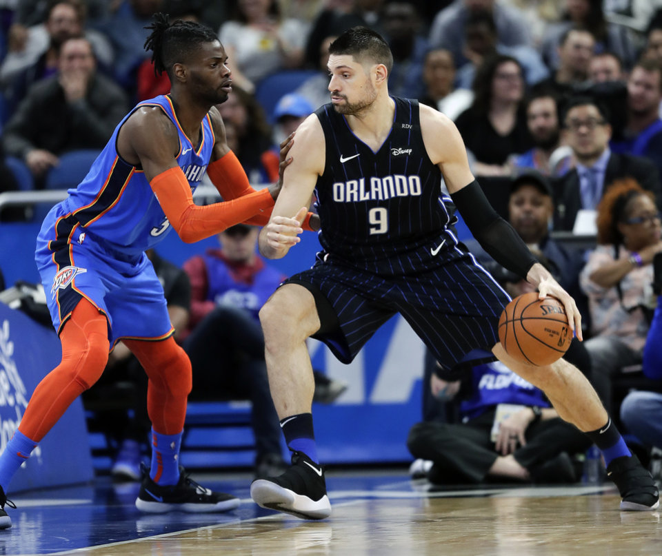 Photo - Orlando Magic's Nikola Vucevic (9) goes to the basket against Oklahoma City Thunder's Nerlens Noel, left, during the first half of an NBA basketball game, Tuesday, Jan. 29, 2019, in Orlando, Fla. (AP Photo/John Raoux)