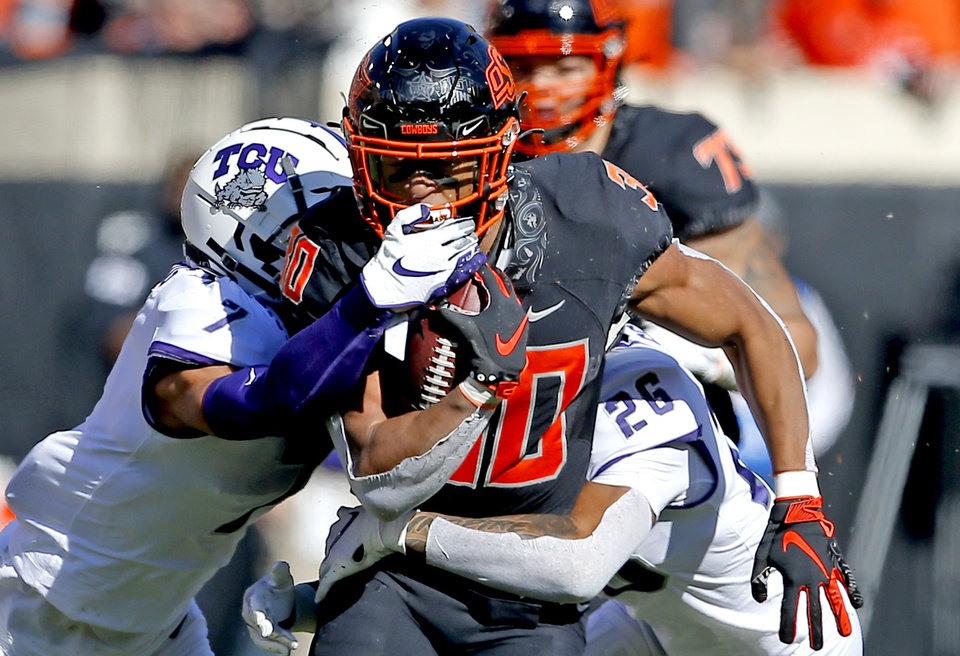 Photo - Oklahoma State's Chuba Hubbard (30) is tackled by TCU's Trevon Moehrig (7) and Vernon Scott (26) in the first quarter during the college football game between the Oklahoma State University Cowboys and the TCU Horned Frogs at Boone Pickens Stadium in Stillwater, Okla.,  Saturday, Nov. 2, 2019. [Sarah Phipps/The Oklahoman]