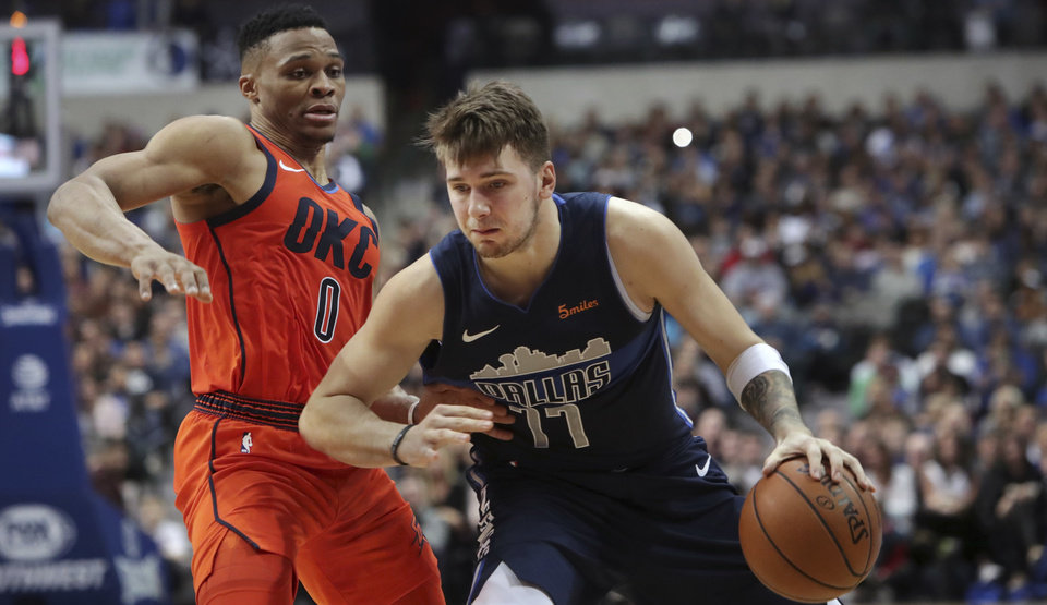 Photo - Dallas Mavericks forward Luka Doncic (77) drives past Oklahoma City Thunder guard Russell Westbrook (0) during the second half of an NBA basketball game in Dallas, Sunday, Dec. 30, 2018. The Mavericks won 105-103.(AP Photo/LM Otero)