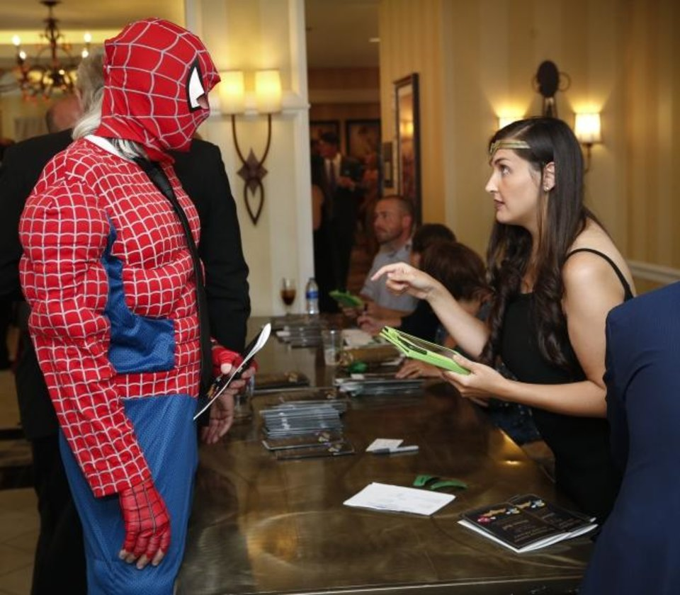 Photo -  Hobie Higgins, dressed as Spider-Man, checks in with Constanzia Nizza during the Oklahoma Institute for Child Advocacy's Heroes Ball. [Nate Billings/The Oklahoman]