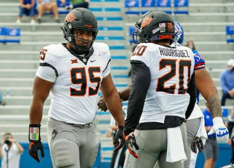 Photo -  Oct 3, 2020; Lawrence, Kansas, USA; Oklahoma State Cowboys defensive tackle Israel Antwine (95) reacts after making a play with linebacker Malcolm Rodriguez (20) during the first half against the Kansas Jayhawks at David Booth Kansas Memorial Stadium. Mandatory Credit: Jay Biggerstaff-USA TODAY Sports