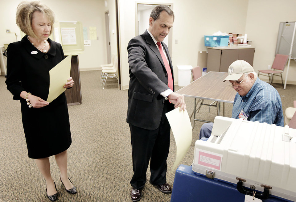 Photo - Randy Brogdon places his ballot in the ballot box as his wife Donna waits her turn after voting in the Oklahoma primary election at Faith Lutheran Church in Owasso  July 27, 2010. Looking on is inspector Wayne Harvey. MIKE SIMONS/Tulsa World