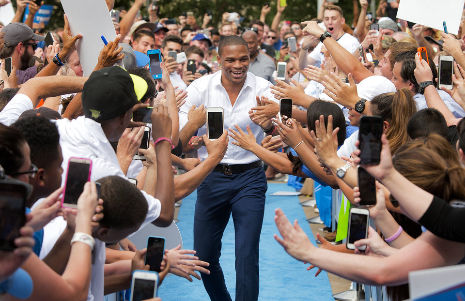 Photo -  Oklahoma City Thunder point guard Russell Westbrook is greeted by fans as he arrives Thursday for a news conference to announce a contract extension with the team at the Chesapeake Energy Arena. [Photo by Chris Landsberger, The Oklahoman]