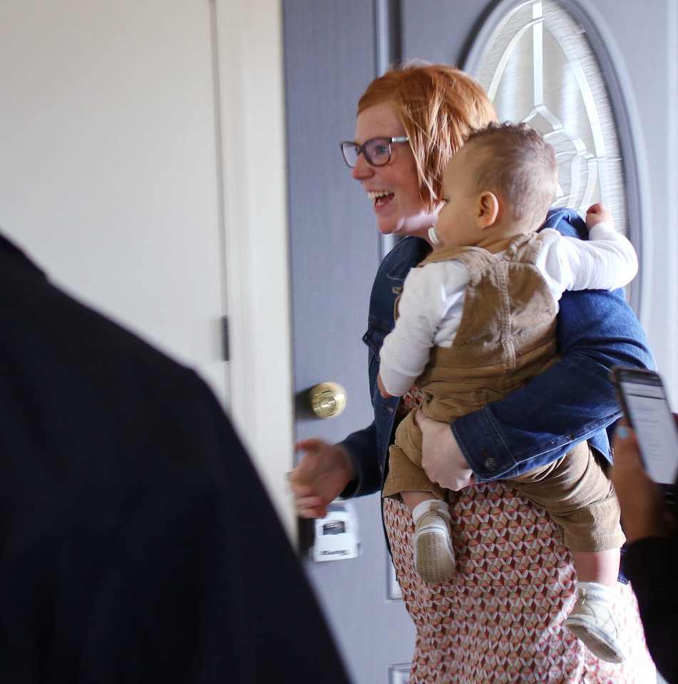 Photo - Brittani Githiri holds her one year old son, Piaget, as she enters her finished house. [Photo by Doug Hoke/The Oklahoman]