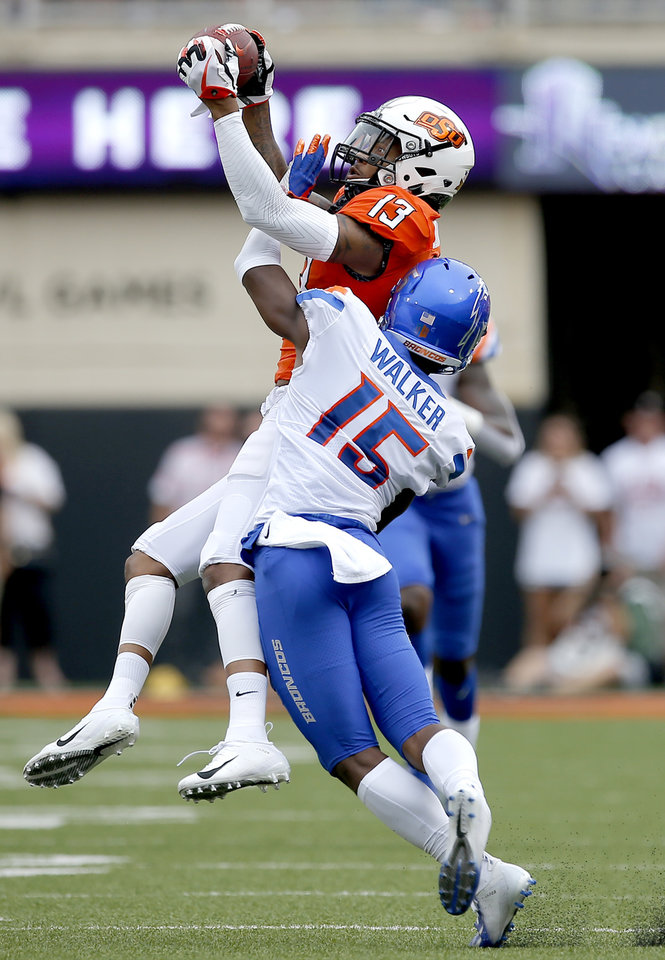 Photo - Oklahoma State's Tyron Johnson (13) makes a catch as Boise State's Jalen Walker (15) defends in the second quarter during a college football game between the Oklahoma State Cowboys (OSU) and the Boise State Broncos at Boone Pickens Stadium in Stillwater, Okla., Saturday, Sept. 15, 2018. OSU won 44-21. Photo by Sarah Phipps, The Oklahoman