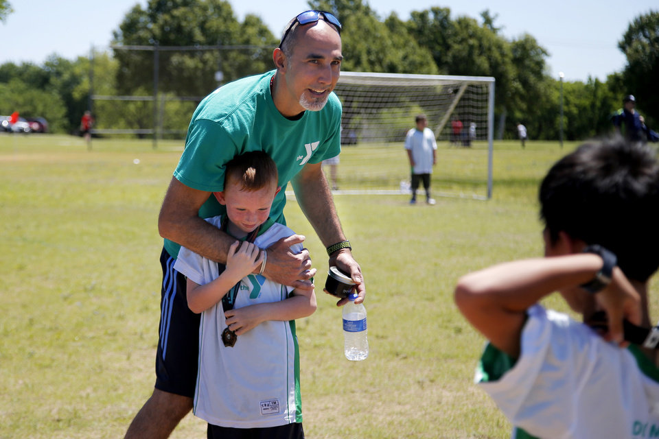 Photo -  Estabraq Al-Adhami hugs one of his players, T.J. Smith, 7, after coaching the last game of the season for his daughter's soccer team in Oklahoma City. [Photo by Bryan Terry, The Oklahoman]
