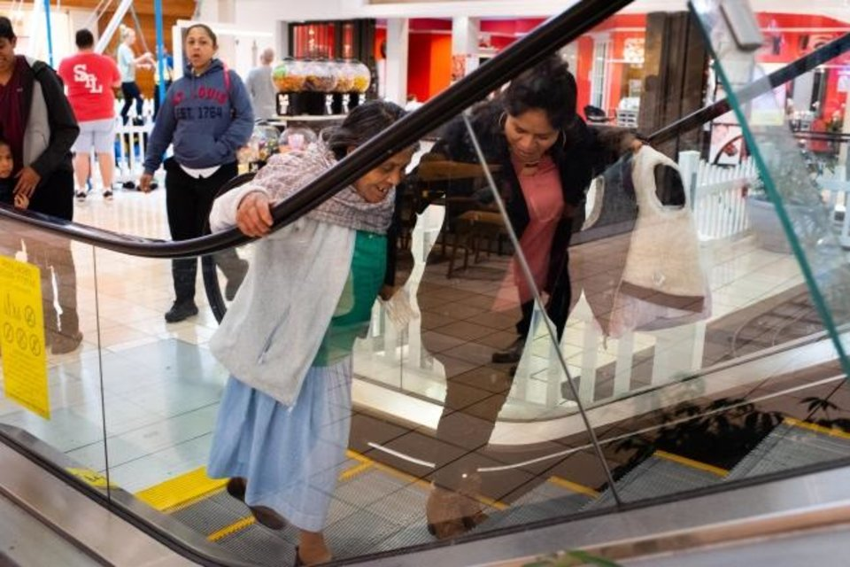 Photo -  Romero León takes her first step onto an escalator at a shopping mall in Fairview Heights, Ill. Her daughter Guillermina Sánchez, 38, helps. [Sarah L. Voisin/The Washington Post]