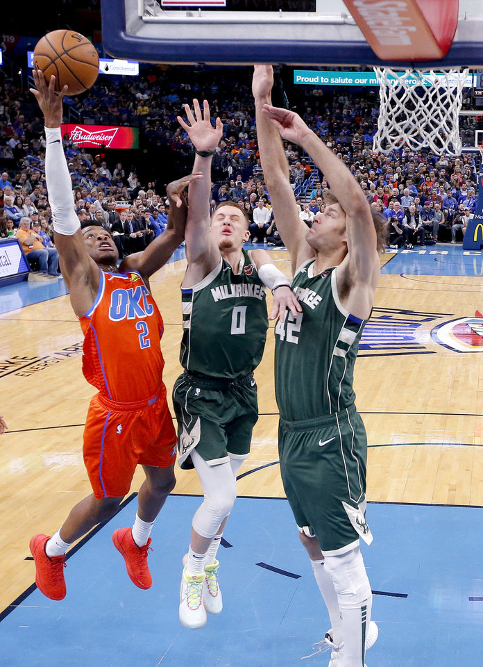 Photo - Oklahoma City's Shai Gilgeous-Alexander (2) goes up for a basket Donte DiVincenzo (0) and Robin Lopez (42) defend during the NBA game between the Oklahoma City Thunder and the Milwaukee Bucks at Chesapeake Energy Arena,   Sunday, Nov. 10, 2019.  [Sarah Phipps/The Oklahoman]