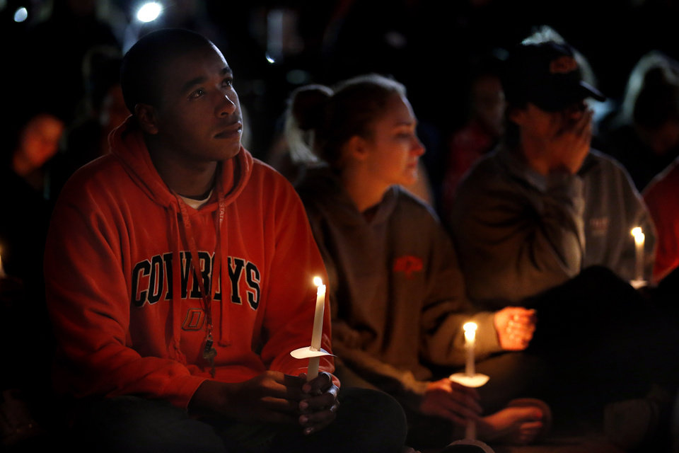 Photo - Oklahoma State University senior William Brown listens to a prayer during a candle light vigil on the campus of OSU,  Sunday, Oct. 25, 2015. The community gathered on the campus to remember those affected by the homecoming fatality crash. Photo by Sarah Phipps, The Oklahoman