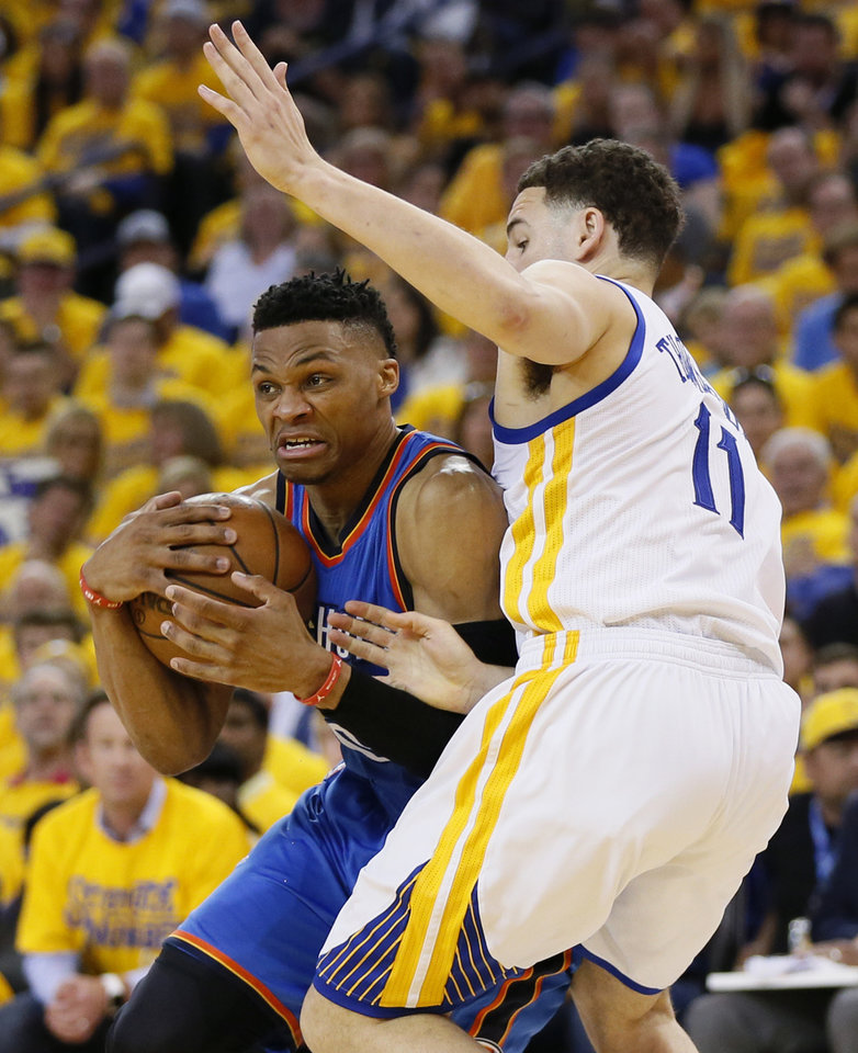 Photo - Oklahoma City's Russell Westbrook (0) tries to get past Golden State's Klay Thompson (11) during Game 2 of the Western Conference finals in the NBA playoffs between the Oklahoma City Thunder and the Golden State Warriors at Oracle Arena in Oakland, Calif., Wednesday, May 18, 2016. Photo by Nate Billings, The Oklahoman