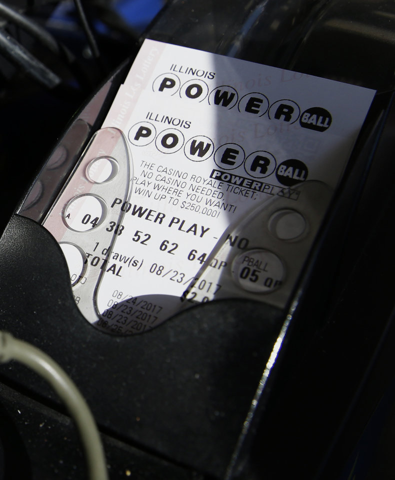 Photo - A Powerball lottery ticket is printed out of a lottery machine at a convenience store Wednesday in Northbrook, Ill. Lottery officials said the grand prize for Wednesday night's drawing has reached $700 million, the second-largest on record for any U.S. lottery game. (AP Photo/Nam Y. Huh)