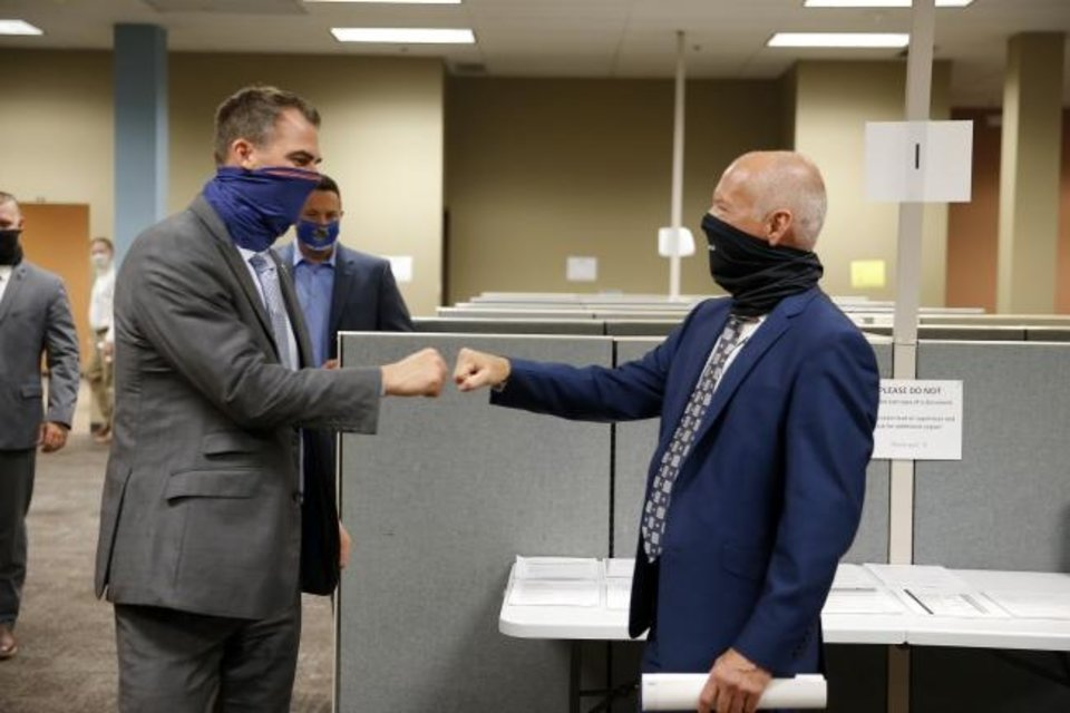 Photo -  Gov. Kevin Stitt greets Oklahoma Health Commissioner Lance Frye before a tour of a  new Oklahoma State Department of Health COVID-19 contact tracing center inside the old Shepherd Mall in Oklahoma City in August. [Bryan Terry/The Oklahoman]