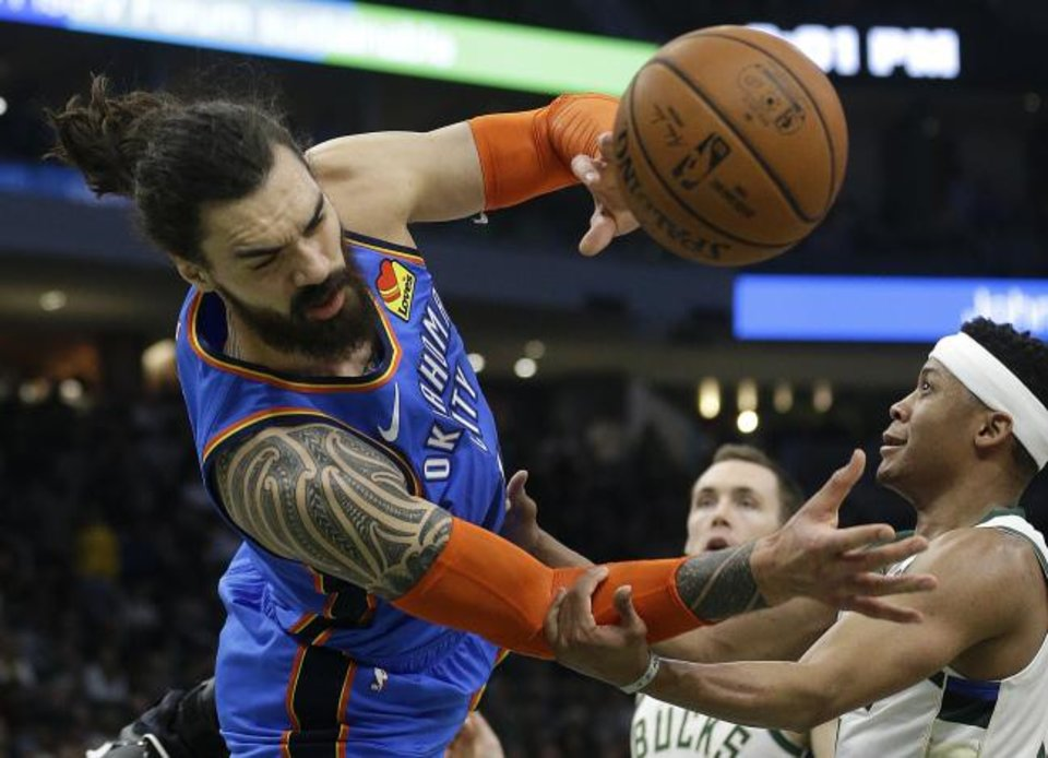 Photo -  Oklahoma City Thunder's Steven Adams, left, is fouled by Milwaukee Bucks' Tim Frazier during the first half of an NBA basketball game Wednesday, April 10, 2019, in Milwaukee. (AP Photo/Aaron Gash)