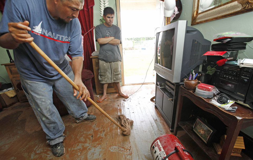 Photo - Abel Borrego mops muddy water from the floor of the living room in his house Friday on the east bank of Lightning Creek near SW 28 and S Santa Fe. PHOTOS BY JIM BECKEL, THE OKLAHOMAN