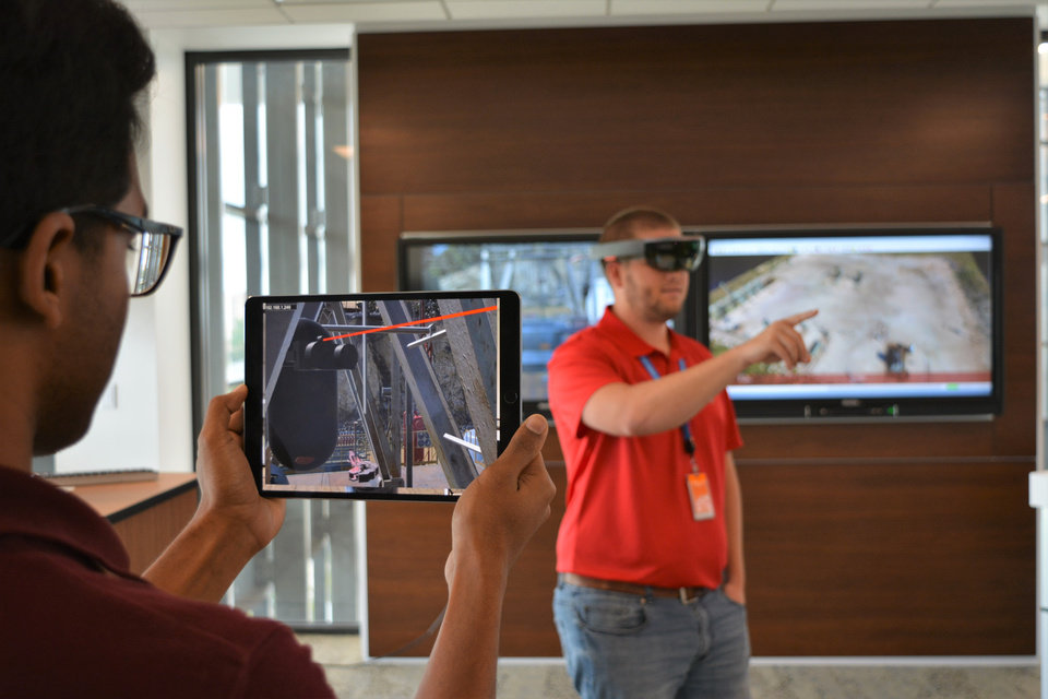 Photo -  Baker Hughes' Rohit Nutalapati and Dustin Sharber use the company's augmented reality software to collaborate in a virtual drilling rig environment using an Apple iPad and Microsoft HoloLens mixed-reality headset. [Photo provided]