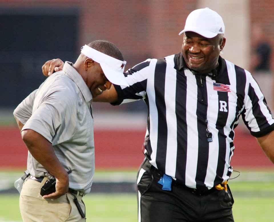 Photo - BW head coach Brad Calip and referee laugh after a conversation over a call during the high school football game between Edmond Santa Fe and Tulsa Booker T. Washington at Wolves Stadium in Edmond, Friday, August 25, 2017. Photo by Doug Hoke, The Oklahoman
