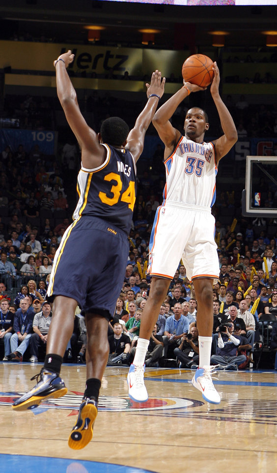 Photo - Oklahoma City's Kevin Durant shoots as Utah's C.J. Miles defends during the NBA basketball game between the Oklahoma City Thunder and Utah Jazz in the Oklahoma City Arena on Sunday, Oct. 31, 2010. Photo by Sarah Phipps, The Oklahoma