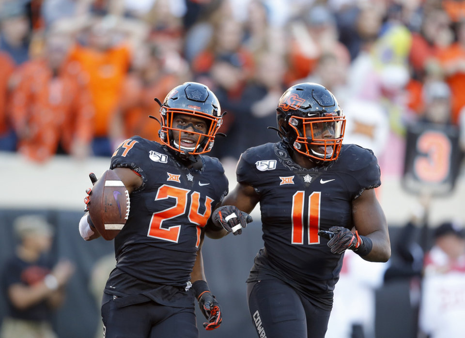Photo - Oklahoma State's Jarrick Bernard (24) celebrates an interception with Amen Ogbongbemiga (11) in the third quarter during the college football game between the Oklahoma State University Cowboys and the TCU Horned Frogs at Boone Pickens Stadium in Stillwater, Okla.,  Saturday, Nov. 2, 2019. OSU won 34-27. [Sarah Phipps/The Oklahoman]
