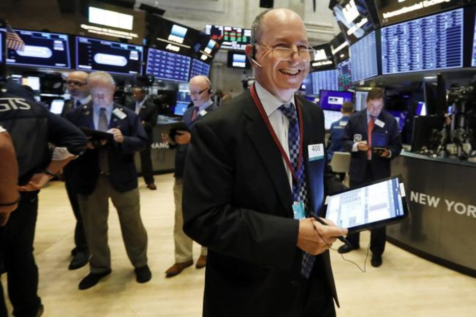 Photo -  Trader Gordon Charlop smiles Wednesday as he works on the floor of the New York Stock Exchange. [AP PHOTO]