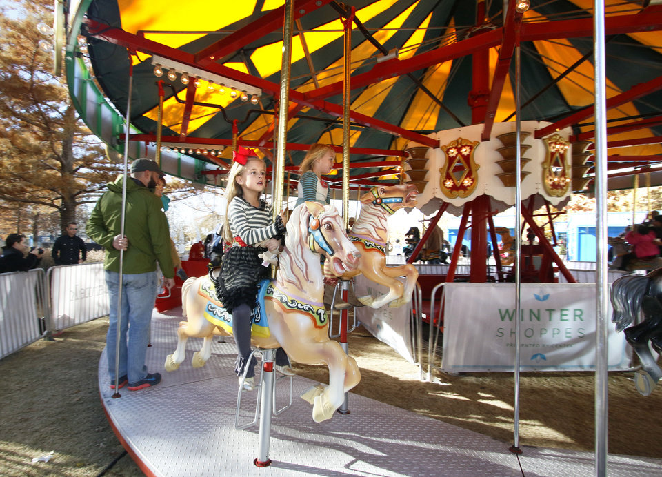 Photo -  Children ride the holiday carousel at the Myriad Gardens during the 2014 Downtown in December in Oklahoma City. [Photo by Paul Hellstern, The Oklahoman Archives]