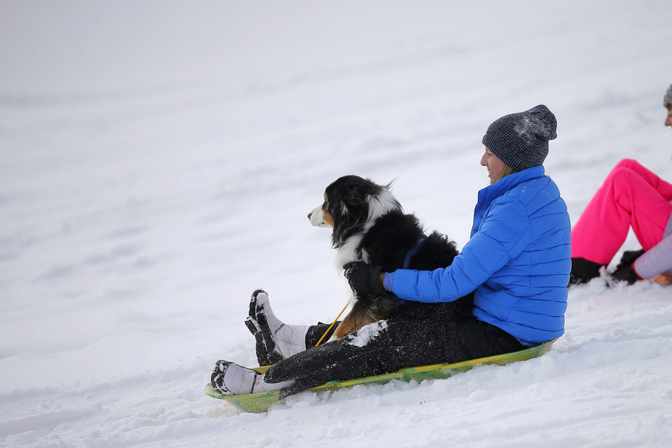 Photo - Courtney Mick and her dog Rumble sled down a hill along W Hefner Road in Oklahoma City after a winter storm dropped another layer of snow in Oklahoma City, Wednesday, Feb. 17, 2021. [Bryan Terry/The Oklahoman]
