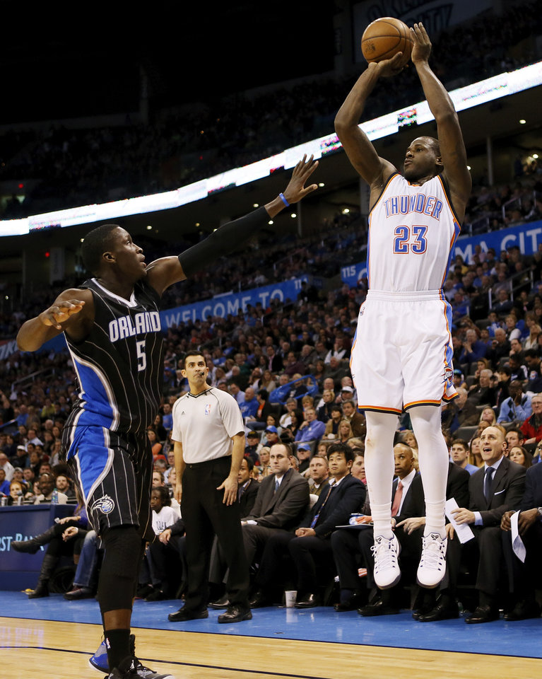 Photo - Oklahoma City's Dion Waiters (23) shoots against Orlando's Victor Oladipo (5) during an NBA basketball game between the Oklahoma City Thunder and the Orlando Magic at Chesapeake Energy Arena in Oklahoma City, Monday, Feb. 2, 2015. Photo by Nate Billings, The Oklahoman