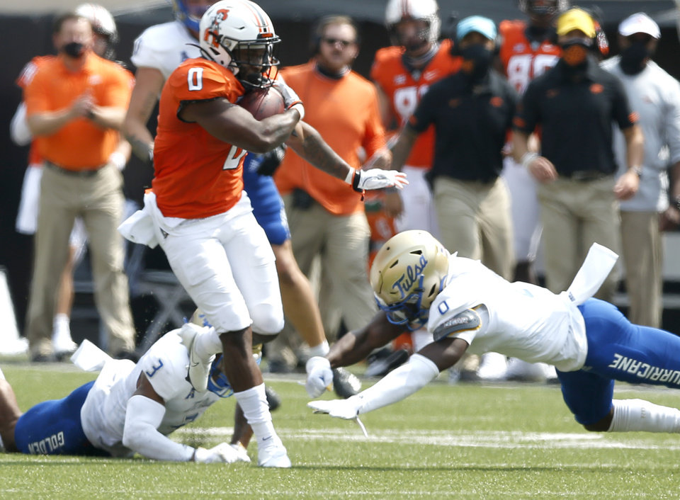 Photo - Oklahoma State's LD Brown gets past Tulsa's Cristian Williams (3) and Tyon Davis during the second half of the season opener at Boone Pickens Stadium in Stillwater on Saturday. Oklahoma State won the game 16-7.  [JOHN CLANTON, TULSA WORLD]