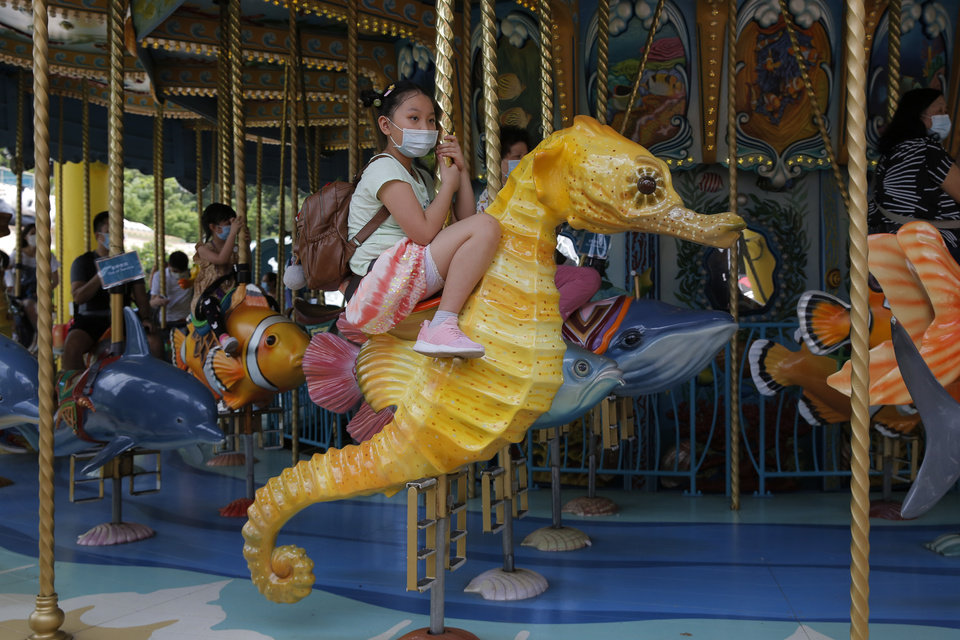 Photo -  Guests wearing face masks to prevent the spread of the new coronavirus, ride on a carousel at Ocean Park in Hong Kong, Saturday, June 13, 2020. Hong Kong Ocean Park reopened Saturday after nearly four months of closure due to the coronavirus pandemic. The animal and nature-themed attraction combines pandas, penguins, roller coasters and other rides, and has been a Hong Kong icon since its opening in 1977. (AP Photo/Kin Cheung)