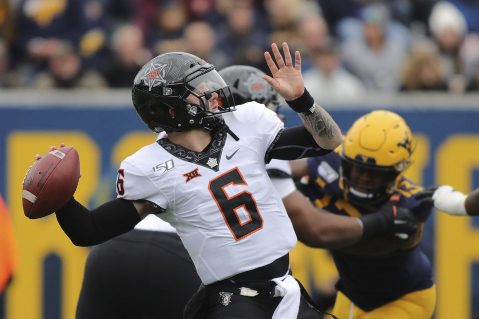 Photo - Oklahoma State quarterback Dru Brown throws during their NCAA college football game against West Virginia  in Morgantown, W.Va., on Saturday, Nov. 23, 2019. [AP Photo/Chris Jackson]