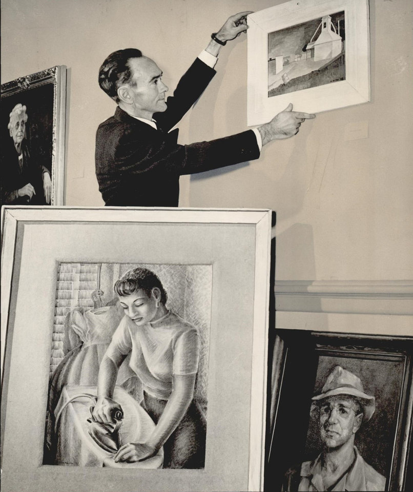 Photo -  Oliver Rearick, a curator at the Oklahoma Art Center in Oklahoma City's Municipal Auditorium (now the Civic Center Music Hall) hangs the first of 200 paintings selected for display in the Association of Oklahoma Artists exhibit on Oct. 26, 1948. [The Oklahoman Archives]