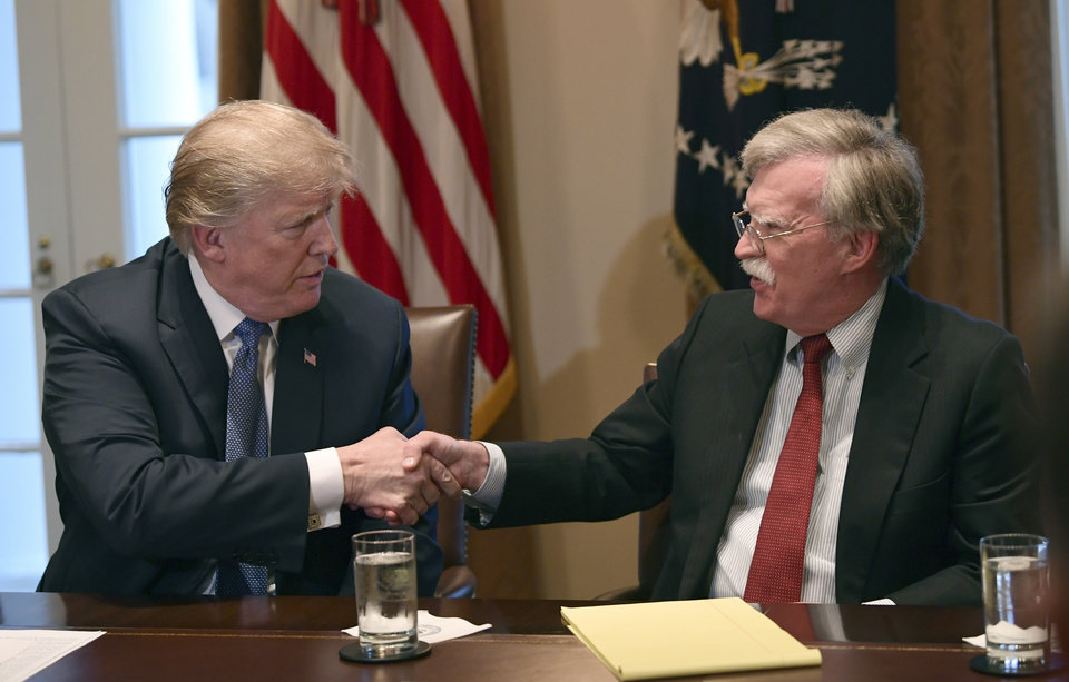 Photo -  In this April 9, 2018, file photo, President Donald Trump, left, shakes hands with national security adviser John Bolton in the Cabinet Room of the White House in Washington at the start of a meeting with military leaders.  Trump has fired national security adviser John Bolton. Trump tweeted Tuesday that he told Bolton Monday night that his services were no longer needed at the White House. [AP Photo/Susan Walsh]