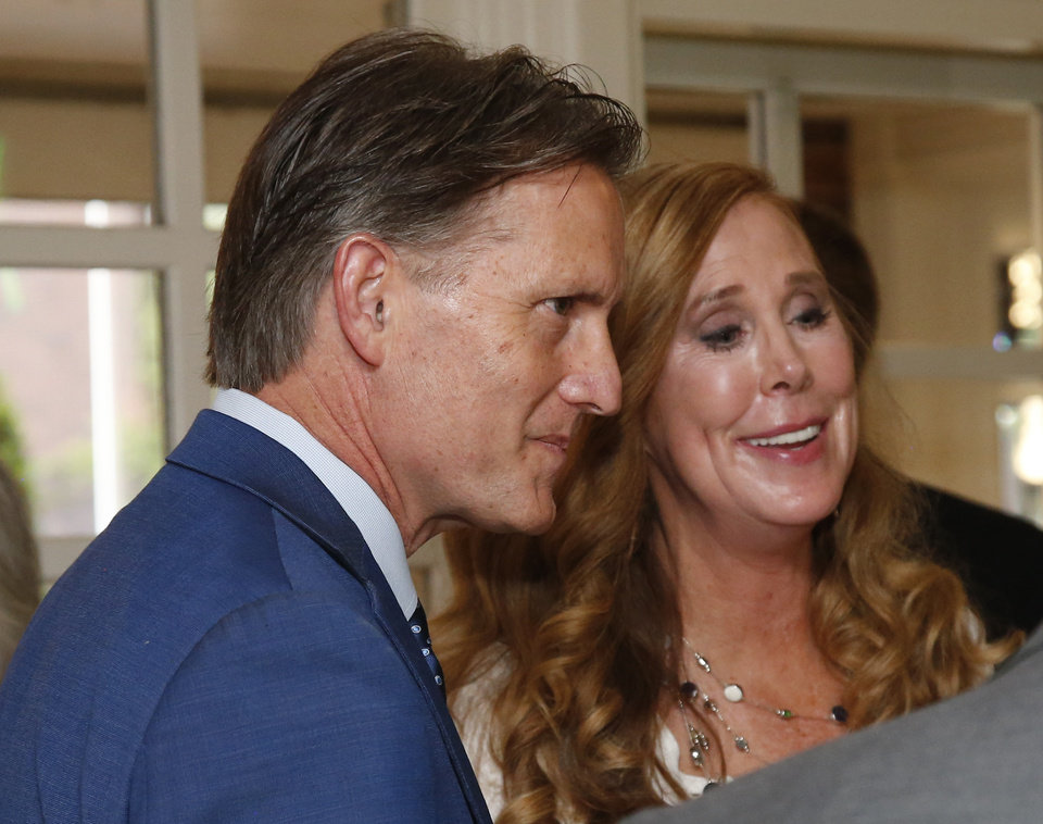 Photo - Mike Hunter, running in the Republican primary runoff for Attorney General, talks with supporters with his wife Cheryl, right, in Oklahoma City, Tuesday, Aug. 28, 2018. (AP Photo/Sue Ogrocki)